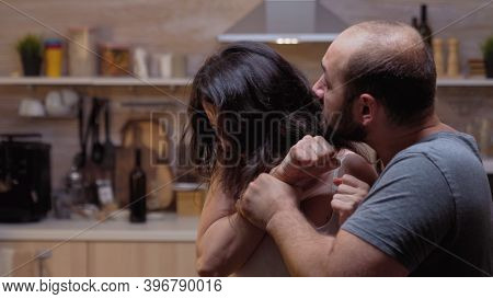Despair Woman Screaming At Alcoholic Husband In The Kitchen. Violent Aggressive Man Abusing Injuring