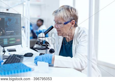 Senior Scientist Conducting Scientific Experiment With Microscope. Elderly Researcher Carrying Out S