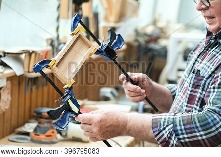 Senior Carpenter Glueing Wooden Craft Surface And Joining With Clamps. Woodwork Carpenter With Equip