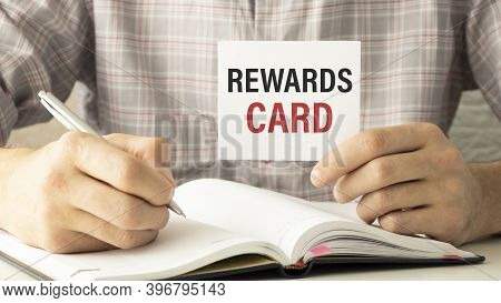 Businessman Putting A Card With Text Rewards Card