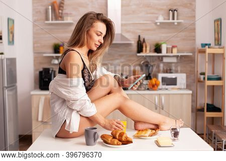 Hot Young Woman Sitting On Kitchen Table Wearing Sexy Lingerie Browsing On Smartphone. Seductive Wom