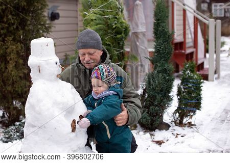 Grandfather And His Small Granddaughter Making Snowman On The Backyard Of Their Country House. Famil