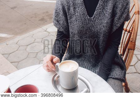 Woman In A Cozy Gray-blue Vest Spends Time Outdoors In The City. Female Sits In Street Cafe On A Woo