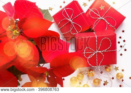 Festive Christmas Card With Red Poinsettia Flower, Wrapped Gifts And Confetti On White Table