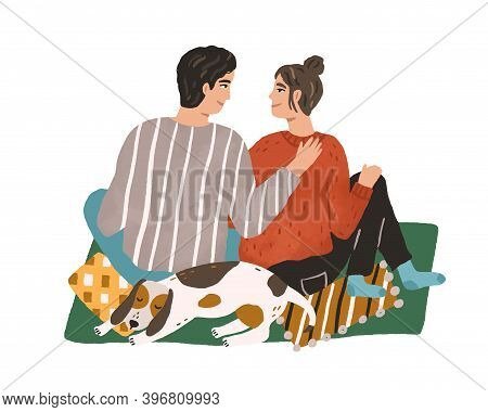 Young Couple Hugging And Sitting On Carpet. Happy Man And Woman Spending Winter Leisure Time Togethe