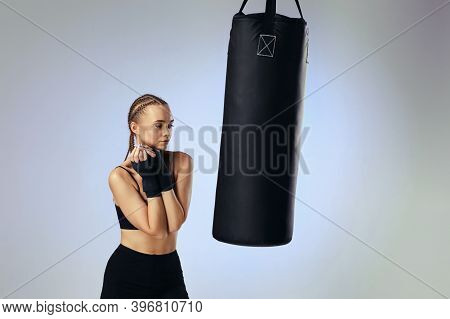 First Workout. Fit Brunette Woman In Sportswear With Boxing Bandages Near Bag On Gray Background. Th