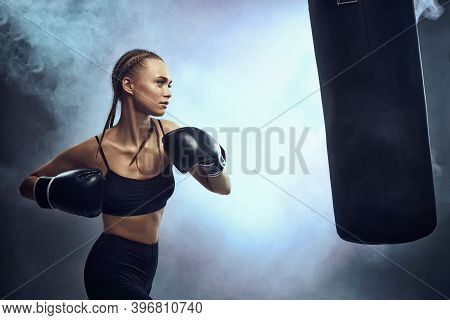 Sporty Brunette Woman In Boxing Gloves And Sportswear Kicking Bag On Dark Background With Smoke.