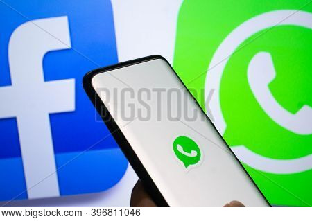 A Mobile Logged Into The Whatsapp Mobile Application Infront Of A Logo Screen