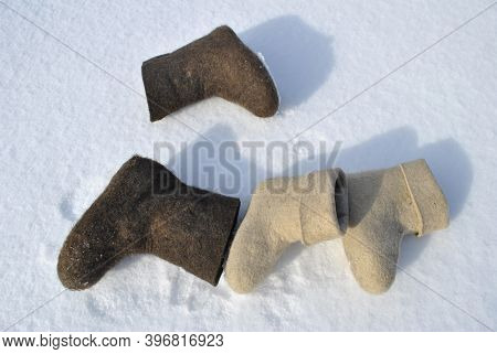 Two Pairs Of Felt Boots Lie In The Snow. Boots Top View.  White And Brown Shoes. Valenoks Are Covere
