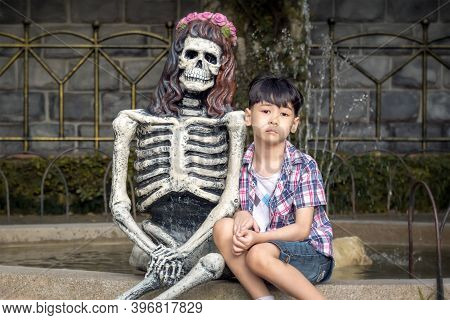Lonely Boy Sits Next To A Skeleton In A Park