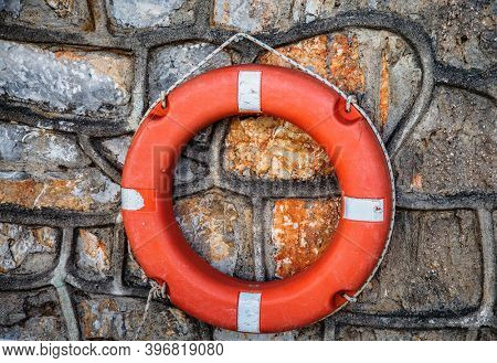 Red lifebuoy on a stone wall. The concept of safety on the waters, first aid for drowning people.