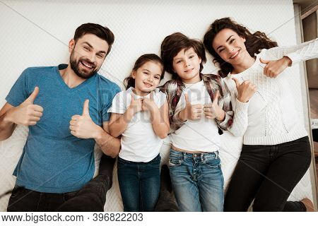 Happy Family Enjoying Of Comfort Lies On Mattress Inside Furniture Store.