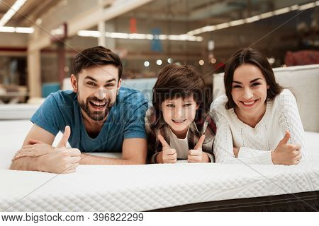 Bearded Man, Together With His Beautiful Wife And Son, Relaxes On The Mattress In The Store.