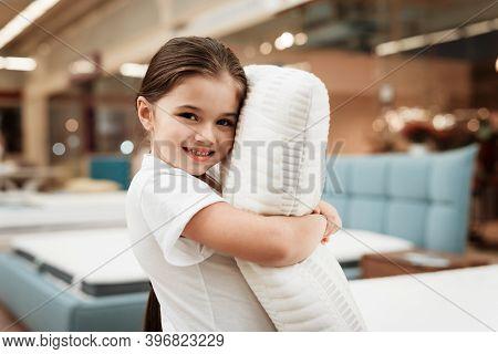 Nice Little Girl Hugs Pillow In Store Of Orthopedic Mattresses. Testing Softness Of Pillow.