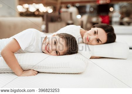 Smiling Little Girl With Beautiful Mother Hugs Pillows In Store Of Orthopedic Mattresses.