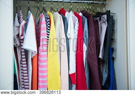 Colorful Clothes On Hangers In Well Organized Wardrobe At Home. Choice Of Cotton Clothes Of Differen