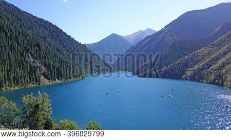 Kolsay Lake Among Green Hills And Mountains. The Mountain Lake Is Surrounded By Green Forest, Tall C