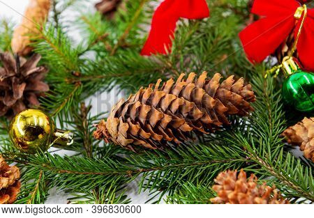 New Year And Christmas Background. The Photo Shows Christmas Tree Branches, Toys, Cones And Other Ch