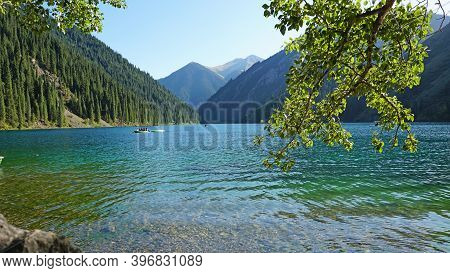 Mountain Lake Kolsay With Floating Boats. View Of Green Hills, Fir Trees, Grass And Water. Boats Wit