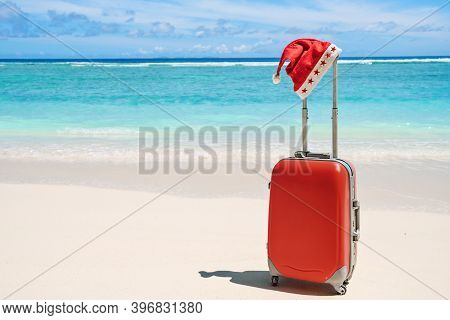 Red Santa Claus Christmas Hat On Handle Of Red Travel Luggage With Tropical Beach And Turquoise Sea