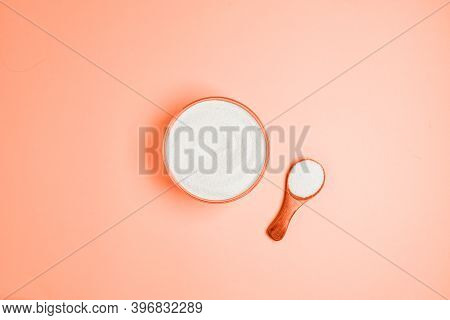 Top View Of Collagen Powder Or Protein In A Glass Bowl And Small Wooden Spoon On Beige Coral Backgro