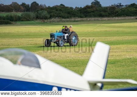 Tractor Driving Along The Airfield Runway To Pick Up The Glider. Old Warden, Bedfordshire, Uk , Octo