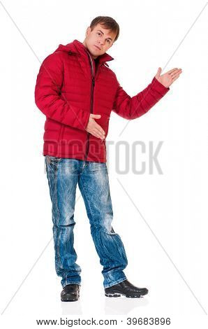 Full length portrait of a young man in winter clothing showing something isolated on white background