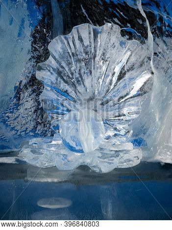 Ice Sculpture Pearl In Open Shell On Blurred Ice Background