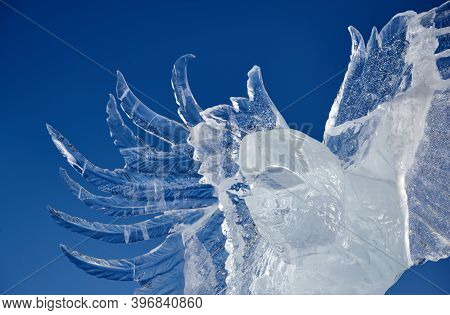 Abstract Ice Sculpture Eagle Spread Its Wings Against The Blue Sky