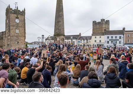 Richmond, North Yorkshire, Uk - June 14, 2020: A Large Group Of Protesters Kneel And Raise An Arm At