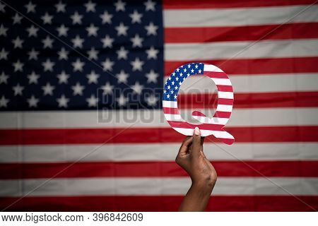Hands Holding Q Alphabet With Us Flag As Background With Copy Space - Concept Qanon Or Q Anon Deep S
