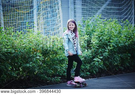 Two Pretty Little Sisters Having Fun Together Learning To Skateboard Outdoors