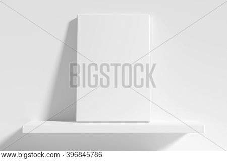 Blank White Empty Rectangular Poster On White Shelf Leaning At Empty White Wall, White Bleached Colo