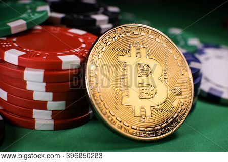 Bitcoin Gold Coin With Poker Chips On A Green Poker Table Against Black Background. Blockchain Casin