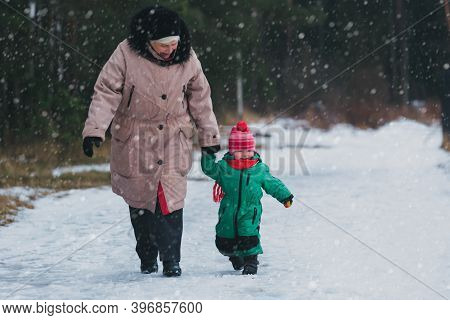Grandmother With Little Granddaughter Walk In Nature, Family Enjoy Winter Snow