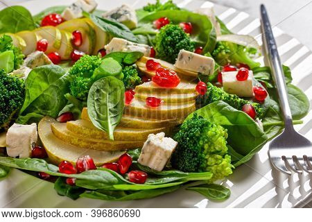 Pear Salad With Blue Cheese Cubes, Broccoli, Spinach, Dried Cranberry And Pomegranate Seeds  On A Pl