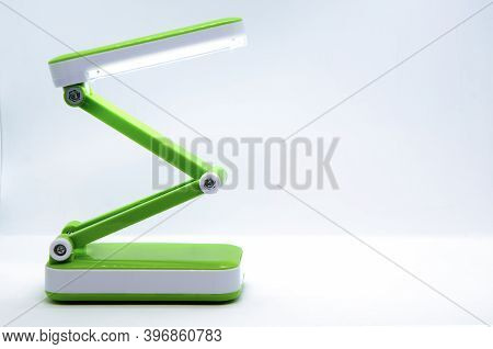 Compact Foldable Portable Led Desk Lamp With Flexible Body Made Of Bright Green Plastic On A White B