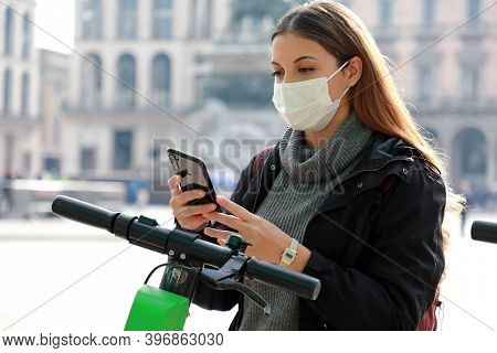 New Eco-friendly Transport. Young Business Woman With Surgical Mask Unlocks E-scooter With Her Mobil
