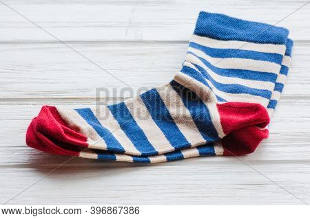 Knitted Striped Socks On Wood Background. Comfort Home Textiles.