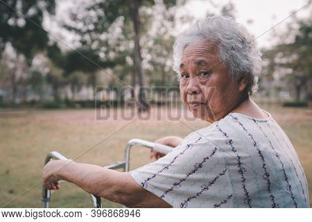 Asian Senior Or Elderly Old Lady Woman Patient Walk With Walker In Park With Copy Space, Healthy Str