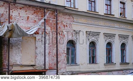 Fragment Of Facade With Ruined Windows And Crumble Stucco Fretwork Of An Old Abandoned Building. Des
