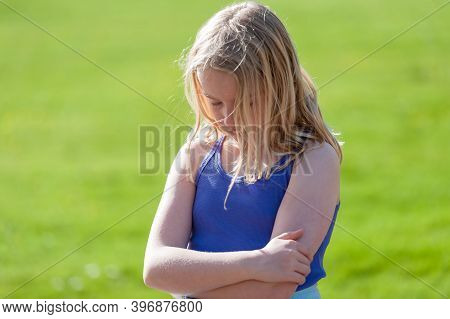 Moody Young Blonde Girl With Arms Folded Sulks In A Field.