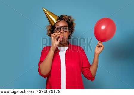 Astonished African Woman Blowing Air Baloon For Birthday Party.
