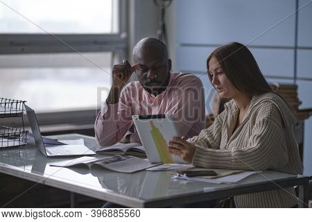 Young African-american Man With Female Colleague While Working In Cubicle At Office. Ethnic Entrepre