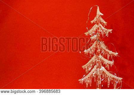 New Year And Christmas Card On A Red Background. Transparent Christmas Tree Made Of Icicles And Chri