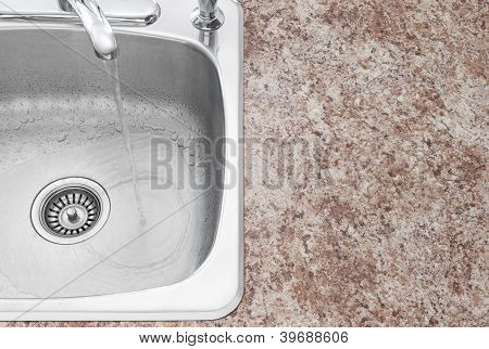 Water Running From Kitchen Faucet And Countertop Detail