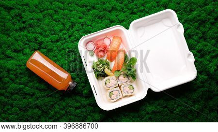 Sushi Set In Takeout Box With Homemade Lemonade On Green Moss Background. Salmon Sashimi, California