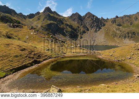 Mountain Lake With Algae Surrounded By Peaks And Mountains In The Pyrenees