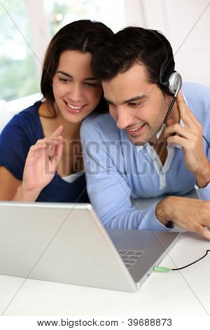 Cheerful young couple chating on internet with webcamera