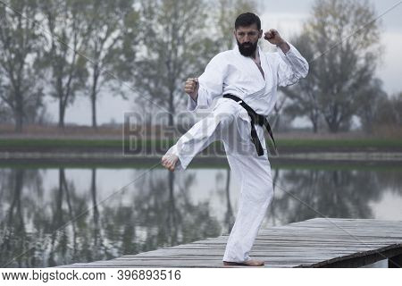 The Bearded Man In White Kimono Is Practicing Karate Martial Arts Outdoors On Lakeshore In The Natur